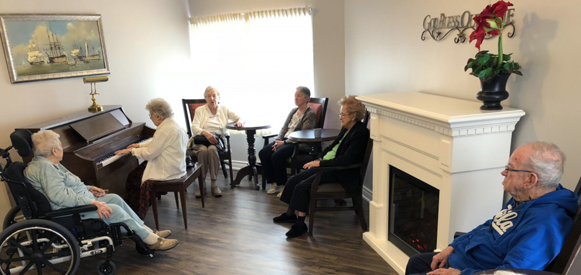 Resident playing piano with group of residents listening